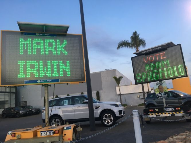 Illuminated signs side by side in Scarborough Beach Road.