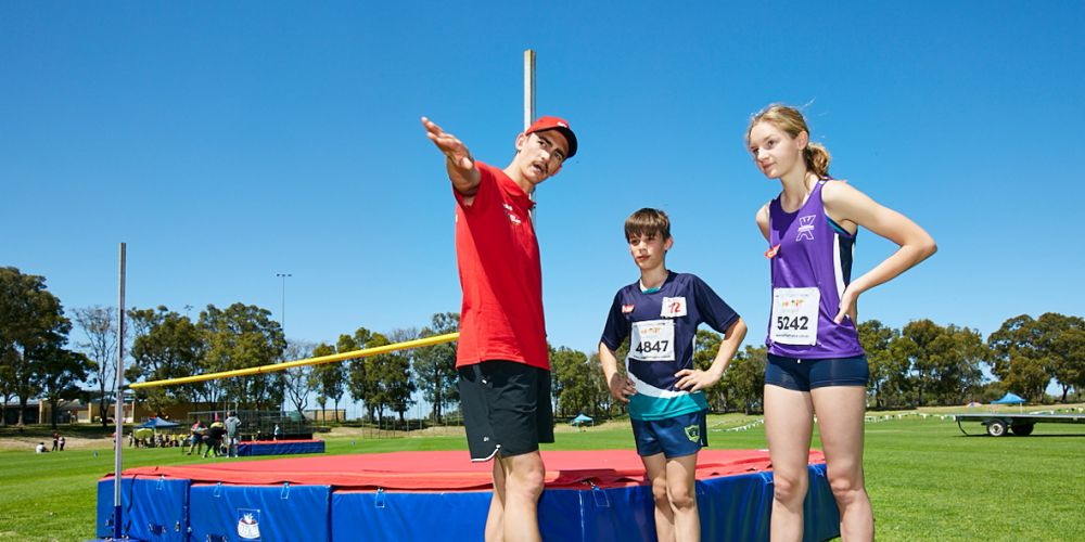 Brandon Starc gives tips to Kingsway Little Athletics high jumpers Oliver Kogiopouos and Charli Woodward. Pictures supplied