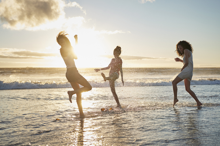 Young women hanging out at the beach, at sunset