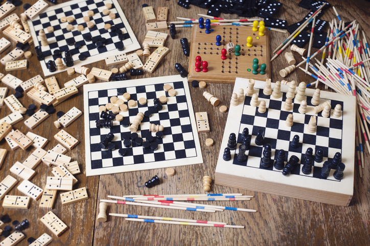 Variety of leisure games  on the table (some dominoes,chess,mikado,game of checkers,some chess boards)