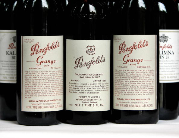 A Penfolds 1962 vintage Cabernet Shiraz, voted number seven in a list of 100 of the world's greatest ever wines, is flanked by 1991 vintage bottles of the famous Penfolds Grange red wine. Picture: AFP Photo/Greg Wood via Getty Images