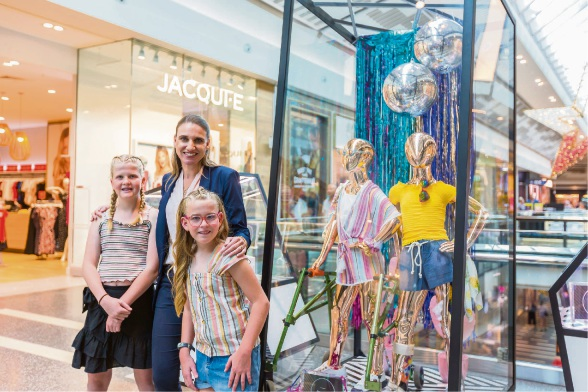 Sisters Reese and Emily J Prior with Lakeside Joondalup centre manager Gemma Hannigan and one of their re-styled display cabinets.