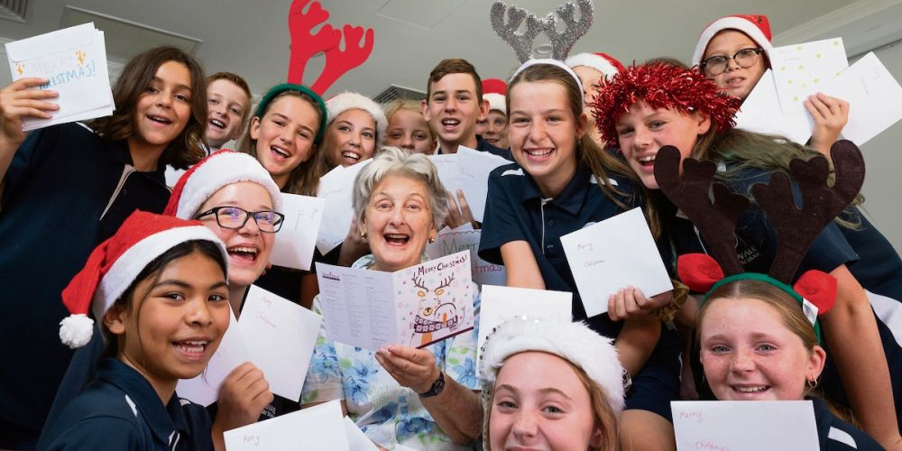 Timberside Villas resident Christine MacFarlan surrounded by Woodvale Primary School students delivering their handmade Christmas cards. Pictures: Tony McDonough
