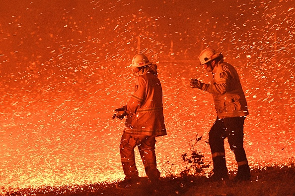Firefighters struggling against the strong wind in an effort to secure nearby houses from bushfires near the town of Nowra in the NSW. Picture: Saeed Khan/AFP via Getty Images