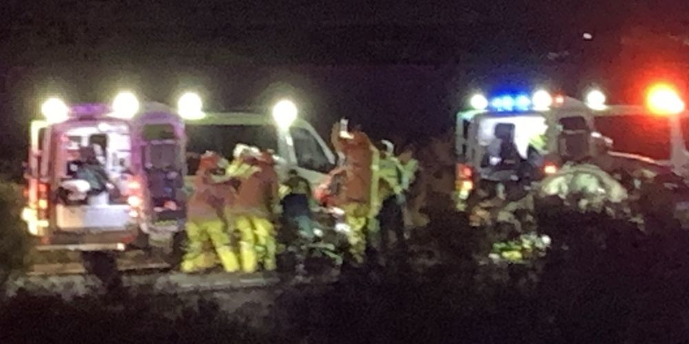 Emergency service crews work on one of the seriously injured in the single car rollover on Kwinana Freeway. Picture: Anton La Macchia