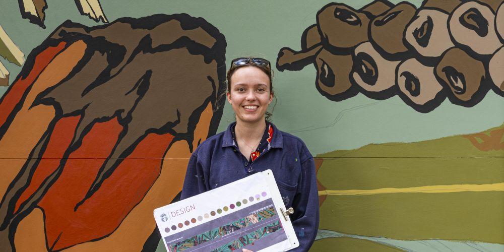 Artist Mikaela Miller in front of the mural at John O'Sullivan Park.