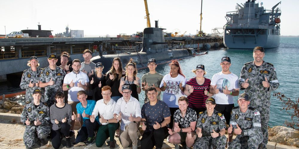 HMAS Rankin Commander Robin Dainty (second left) gives the thumbs up with members from the Submarine Recruiting Team, staff from Defence Force Recruiting and the 2020 National Submariner Tour and Competition winners with HMAS Rankin and HMAS Sirius in the background at Fleet Base West in WA. Picture: Damien Pawlenko/Defence Department