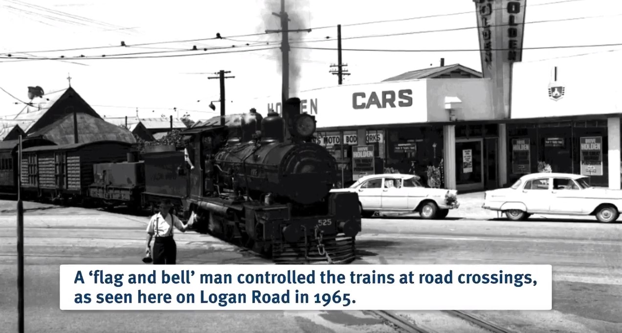 Historical photo of a steam train crossing an intersection in Woolloongabba