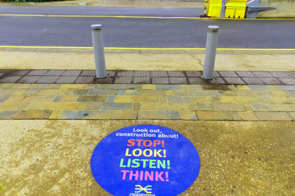 footpath sticker says stop, look, listen, think on a road next to a construction site