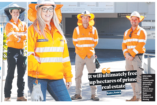 Four construction workers stand apart, in front of a wroksite. The photo is from a newspaper article