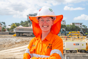 Young woman on a worksite, wearing construction site safety uniform, smiling at the camera