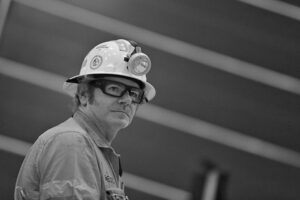 A man wearing a miners hard hat with light attachment. He is in construction safety uniform.
