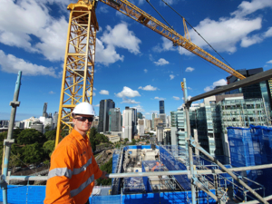 A young worker in safety uniform stands on a worksite on the roof of a skyscraper. the CBD skyline is in the background