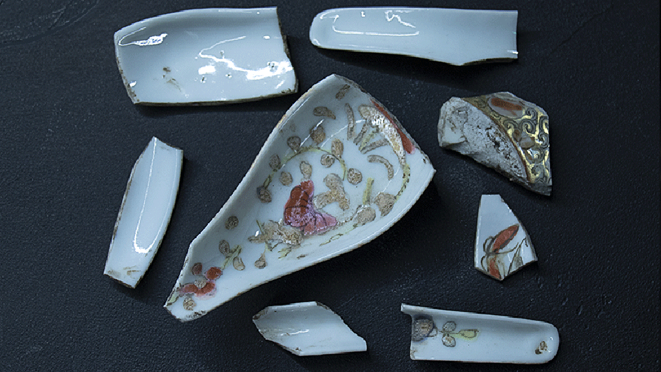 several broken pieces of ceramic tableware. they have a fold and pink filligree design on them
