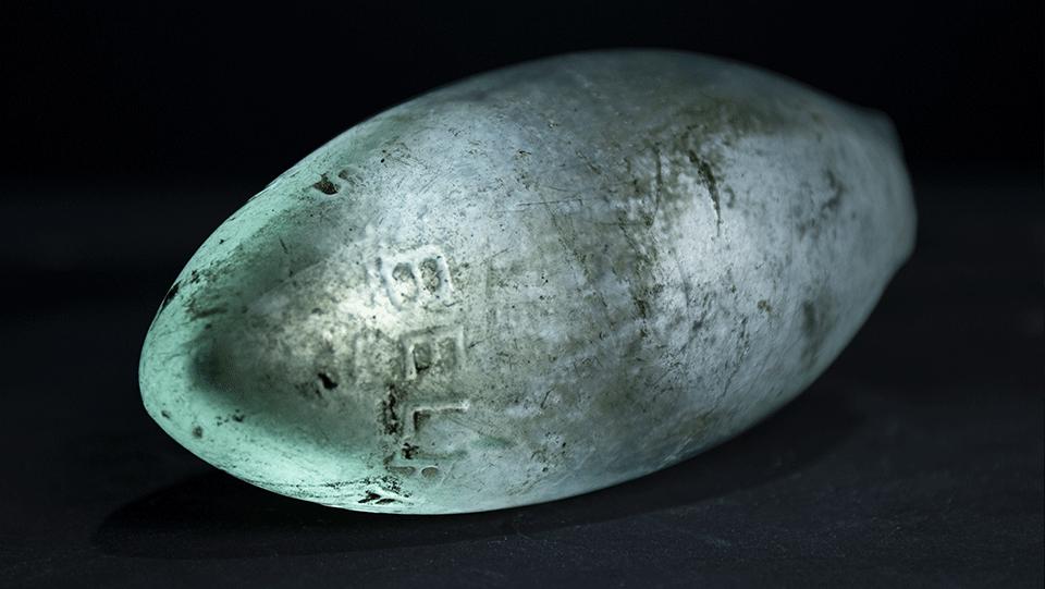 pale translucent glass bottle shaped like a torpedo
