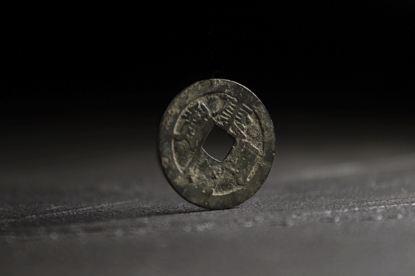 an old coin with a square hole drilled int he middle and characters embossed in the metal