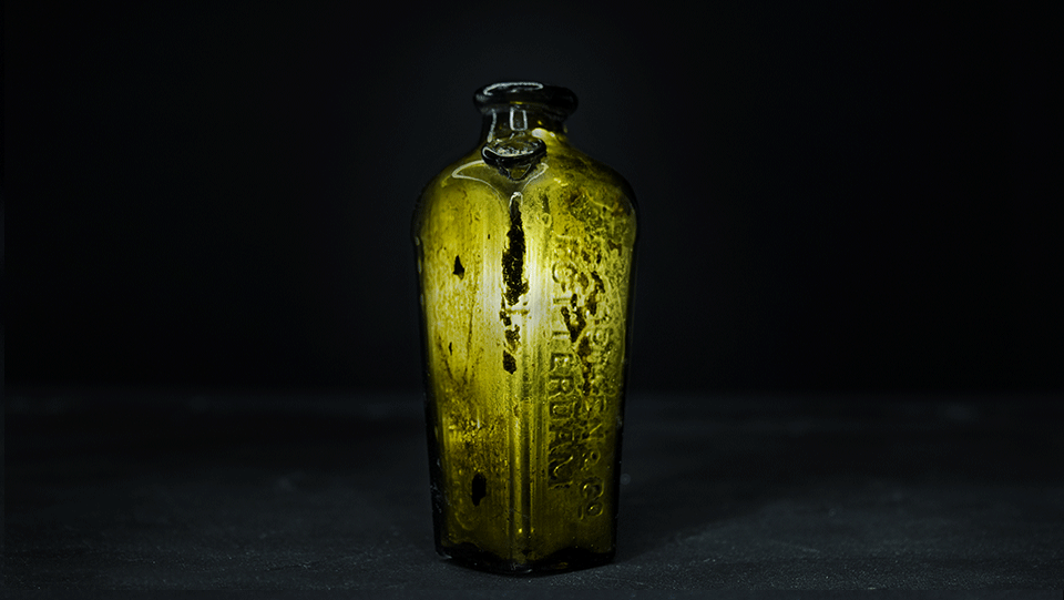 green tinged glass bottle on a dark background