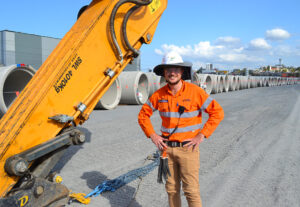 person in orange construction safety uniform next to a large machine.