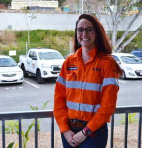Person standing on a verandah smiling. She is in a construction worker uniform