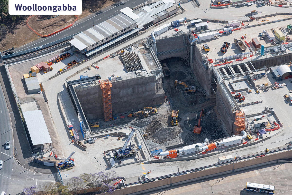 Zoomed in aerial view of the station box excavation at Woolloongabba. Heavy machinery is working deep below ground level