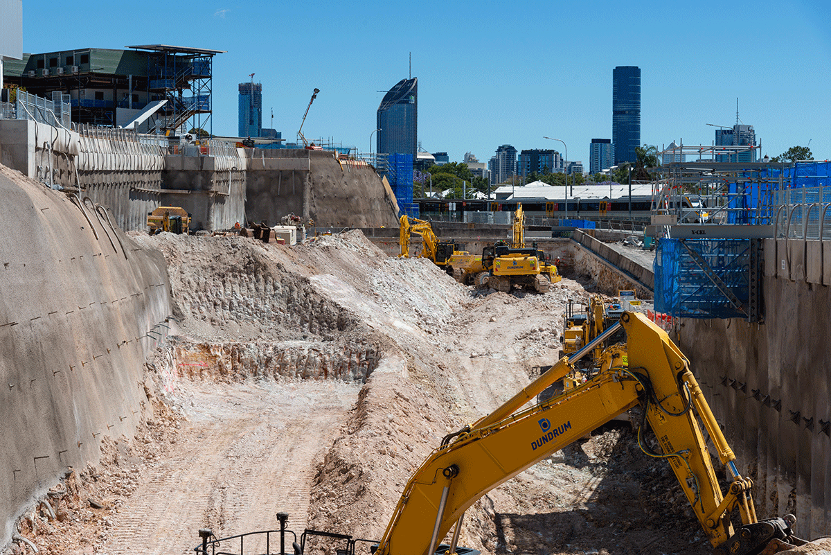 Construction vehicles on the Boggo Road worksite with the Brisbane skyline in the distance