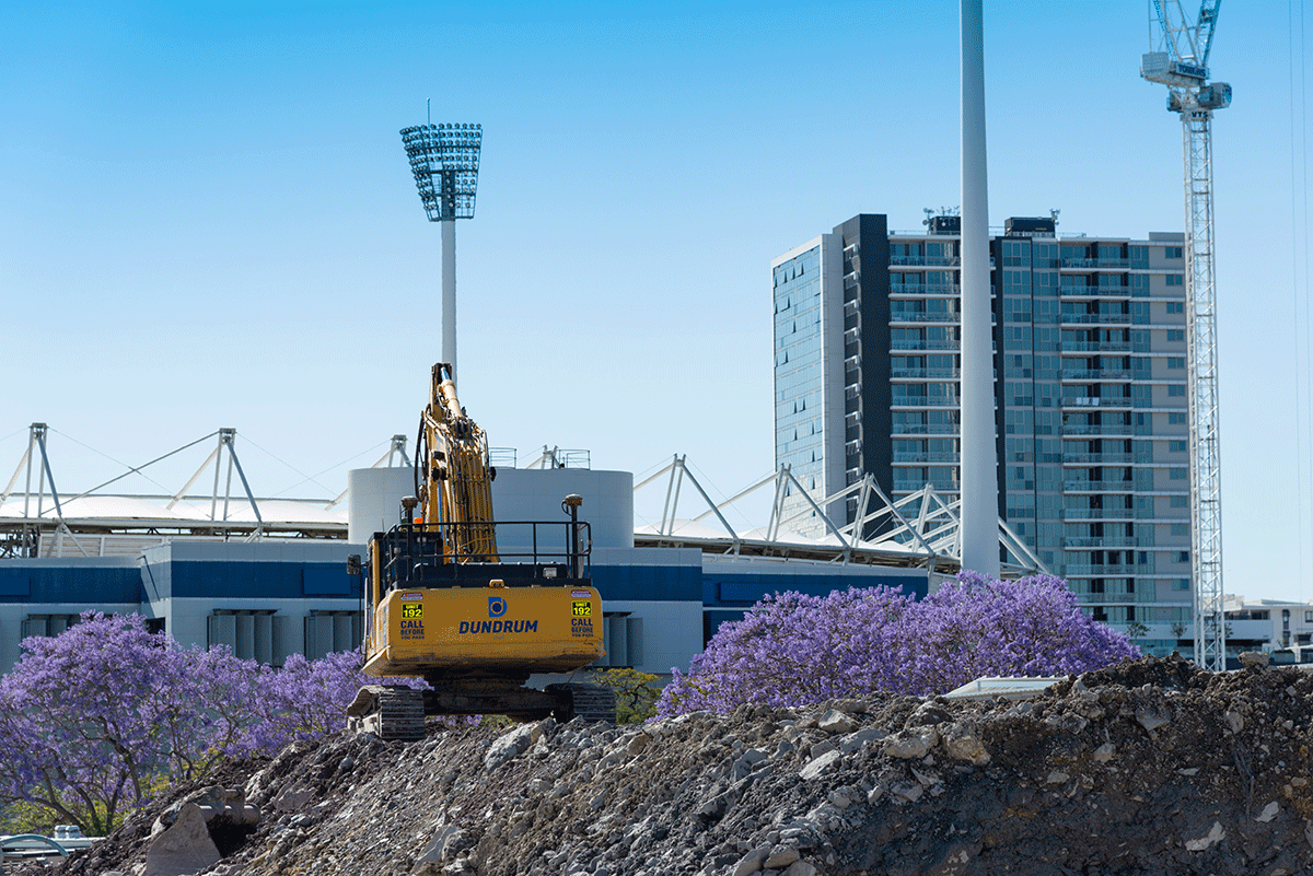 A construction vehicle on top of excavation materials. There are bloomed jacarandas and The Gabba in the background.