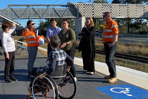 Group of people standing on a train platform. One of the people uses a wheelchair.