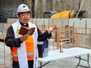 Priest wearing robes, high visibility vest and hard hat reading from the bible as he blesses the Woolloongabba site, Safety fencing and a cement truck are visible in the background