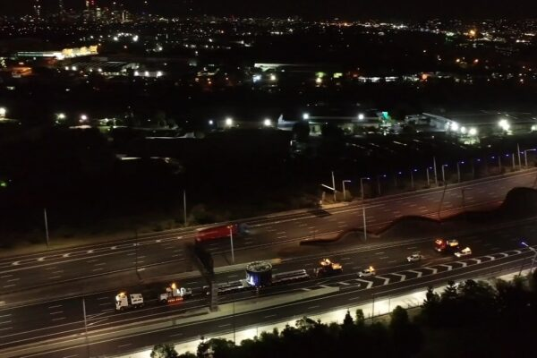 Photo taken from a drone above an empty highway, occupied by a large truck and police escorts