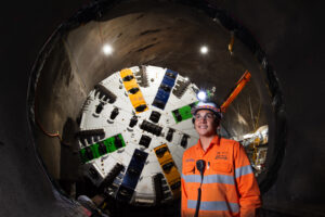 a young person wearing safety helmet and orange construction unform standing iside a tunnel, in front of the TBM