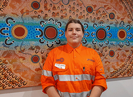 a young person dressed in high visibility construction uniform, standing in front of an indigenous artwork