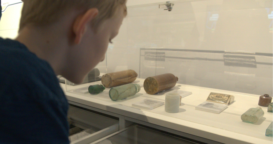 A young person looking into a display case filled with old bottles, jars and objects