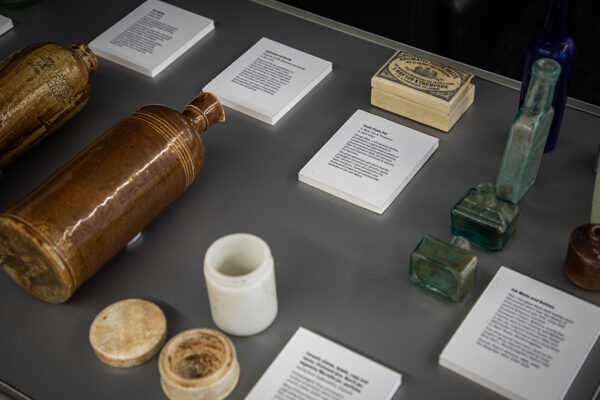 A collection of jars, bottles and containers laid out in a glass case. Description cards are next to each object