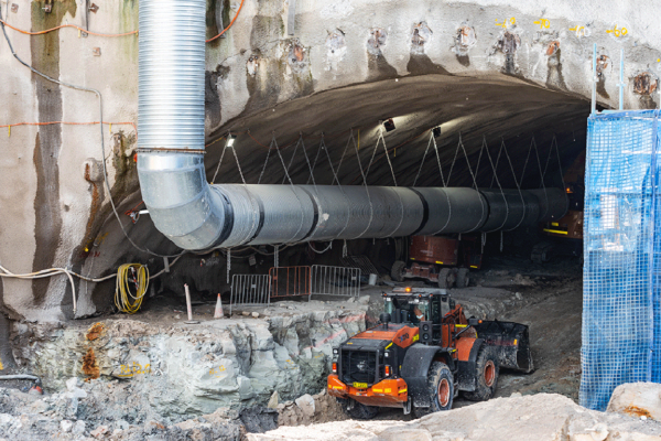 A construction site showing a wide cavern extending into a concrete wall