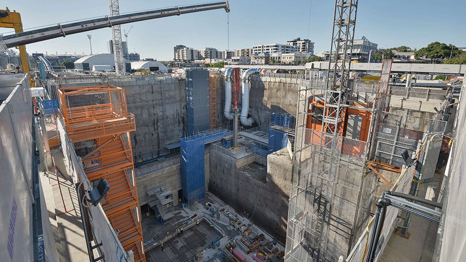 Aerial view looking over the deep excavation and construction of the station box
