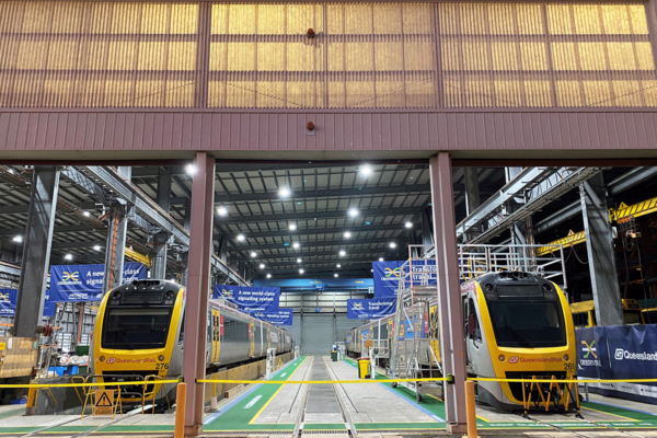 Two trains, side by side in a large, modern warehouse