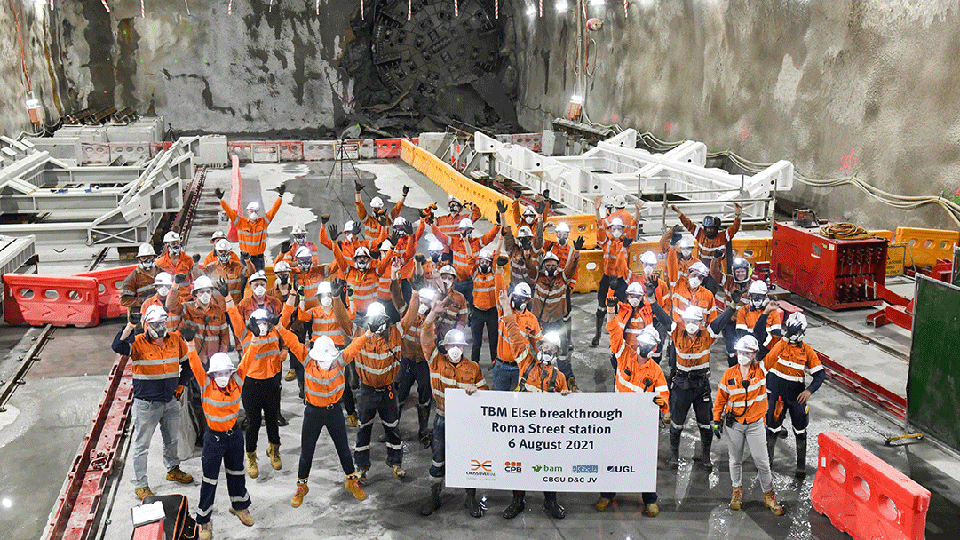 A group of construction workers with their hands in the air, standing in the middle of an empty cavern