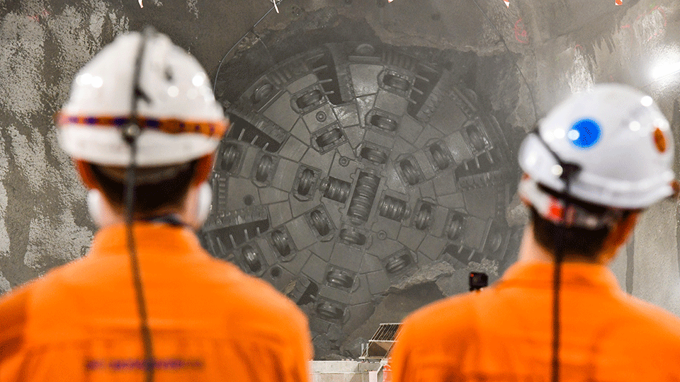 Two construction workers watch on as the TBM cutterhead clears the headwall