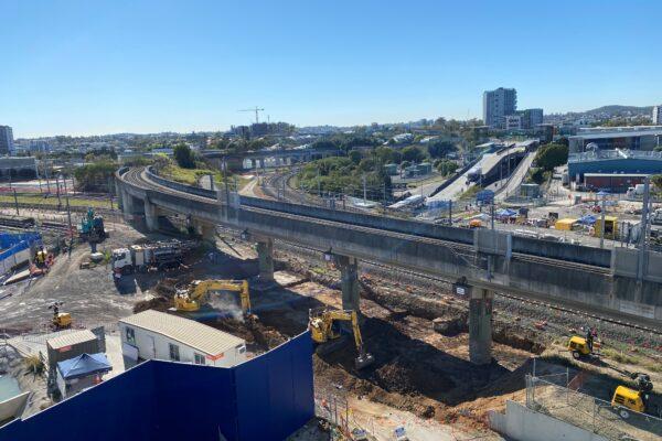 Aerial image of excavators working beneath the existing freight rail bridge