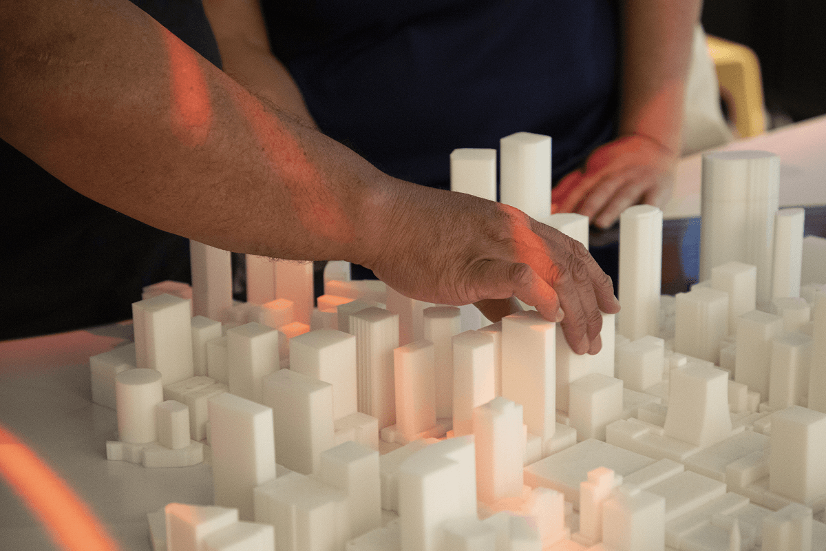 A person with low vision feeling a 3D tactile model of Brisbane City at the Cross River Rail Experience Centre