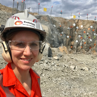 White woman in hard hat, safety goggles and ear defenders, standing in a quarry