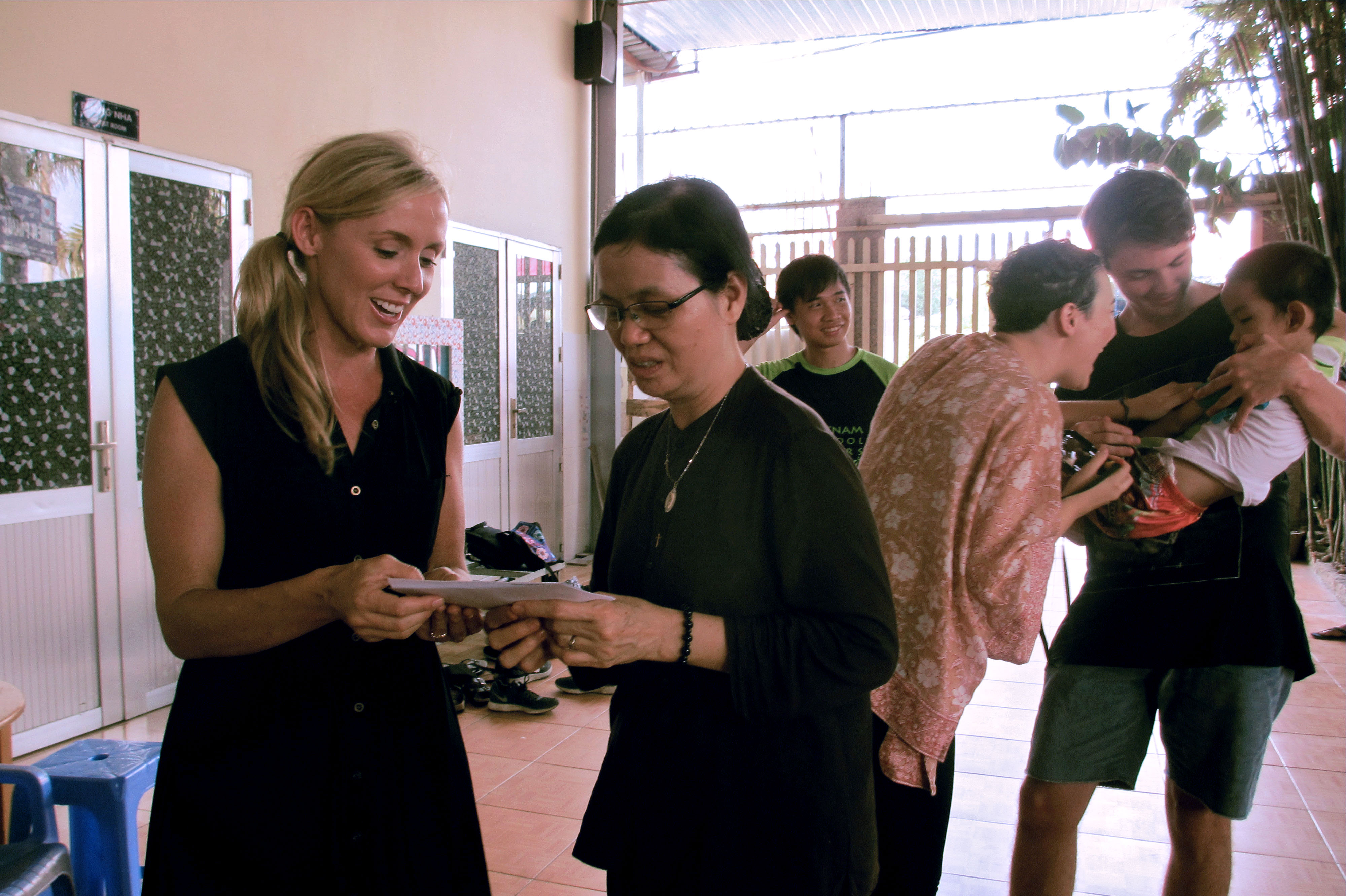 Mrs Lowe handing over a cheque to the Nun in charge of the orphanage
