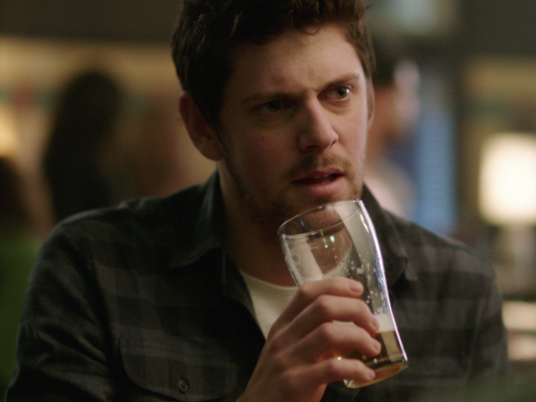 Man with a beer in his hand and a questioning look on his face