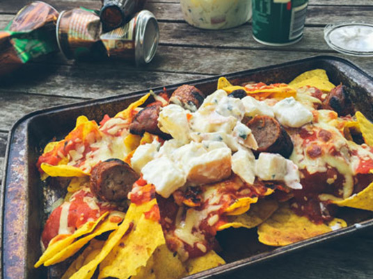 Nachos laying in an oven dish with some empty cans laying behind it