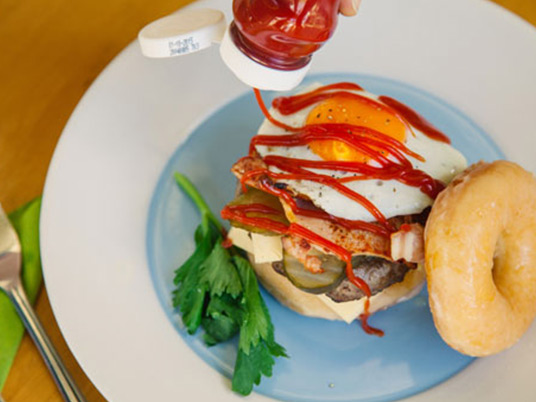 A donut burger with and individual pouring tomato sauce over it