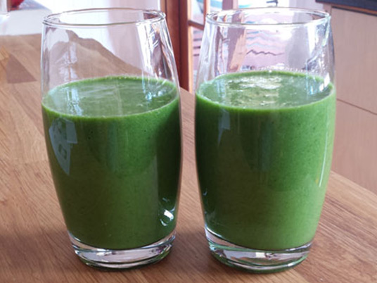 Two glasses next to each other with a green smoothie liquid in them