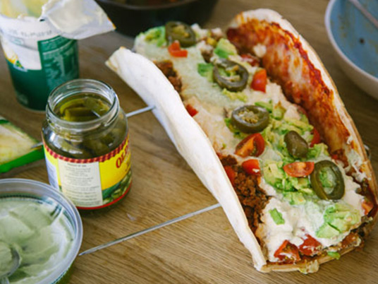 An italian taco with a jar of pickles next to it on a wooden bench