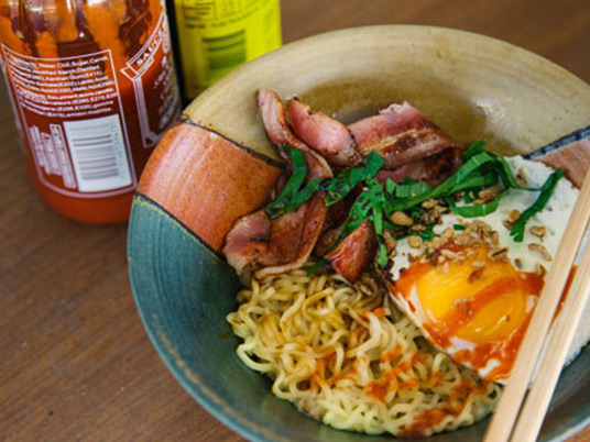 Noodles, egg and bacon in a bowl with a pair of chopsticks laying across the bowl