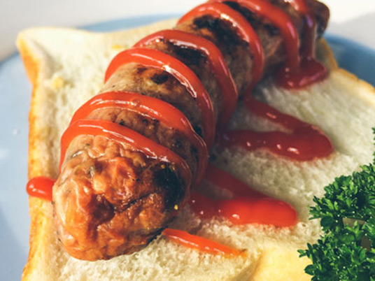A sausage laying on a white piece of bread with tomato sauce on top