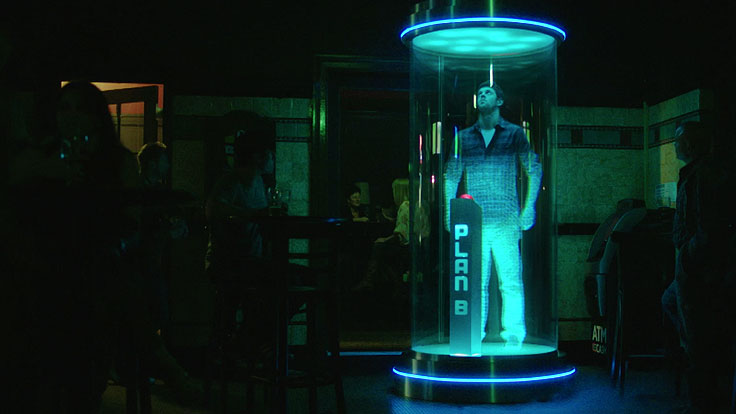 Man looking up to the roof with his hands by his side, while inside a glowing glass chamber representing a teleportation device